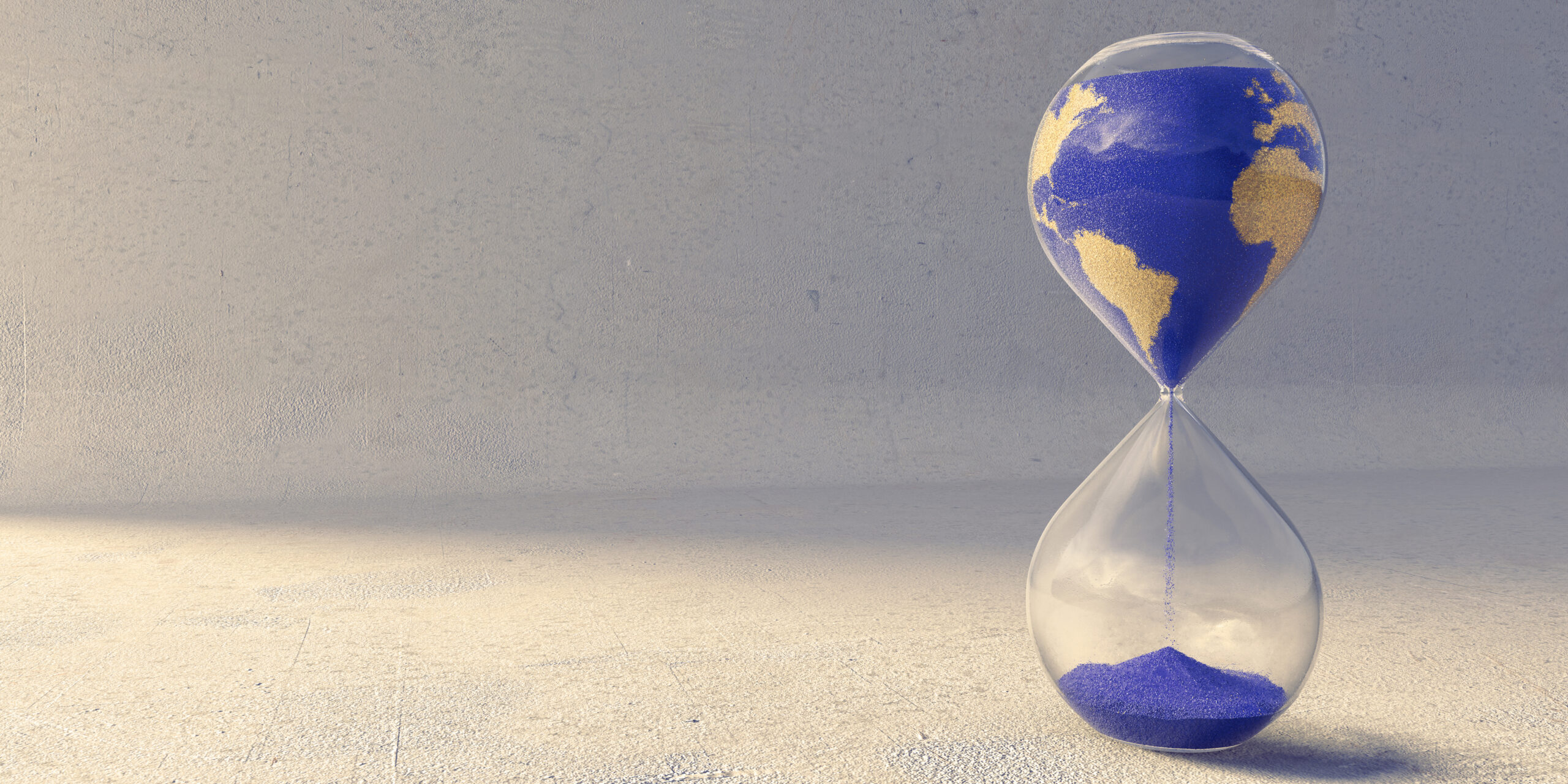 A close up image of an hourglass filled with blue and yellow sand, in the pattern of the countries of the earth. Sand is slowly trickling from the top to pile up in the bottom chamber over time. The timer sits on a rough textured concrete floor near wall.